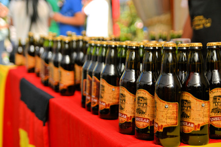 Puerto Varas, Chile - 17 January 2013: Bottles of local craft beer aligned in a row at Prosit fest, an Octoberfest style German festival in a beer tent in Puerto Varas. Descendants of German settlers are still practising their traditions in Southern Chile Editorial