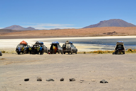 background summer: Uyuni, Bolivia - 27 November 2012: Tourist Jeeps stop for a break and Sightseeing at Laguna Verde in Eduardo Avaroa National Park. Southwestern Bolivia is well-known for dramatic landscapes, lagunas, geysirs, desert and volcanoes