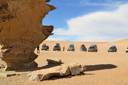 background summer: Uyuni, Bolivia - 27 November 2012: Tourist Jeeps stop at an impressive rock formation called arbol de piedra in Eduardo Avaroa National Park. Southwestern Bolivia is well-known for dramatic landscapes, lagunas, geysirs, desert and volcanoes