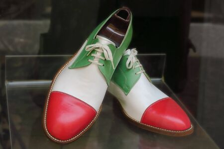 brogues: Handmade leather shoes in colors of Italian flag on display in cobbler shop. Mantova, Italy.