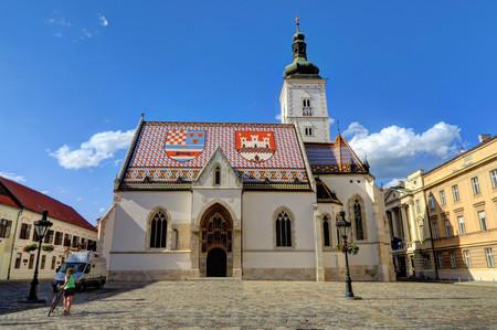 ZAGABRIA CROAZIA 29 giugno 2017: Un ciclista non identificato e la chiesa di St Markin St Mark's Square il 29 giugno 2017, a Zagabria, la Croazia. Archivio Fotografico - 88516458