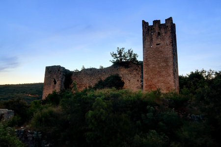 Towers and walls of the ruins of abandoned Dvigrad Castle of Istria in Croatia, at dusk