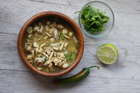 Pozole (Hominy), cilantro (coriander), jalapeno peppers, onions, tomatillo, lime, and pork with wax moth larvae