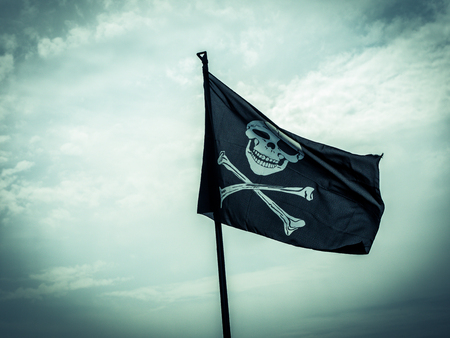 photo shows a pirate flag depicting a skull-and-crossbones with stormy cloudy sky at the background
