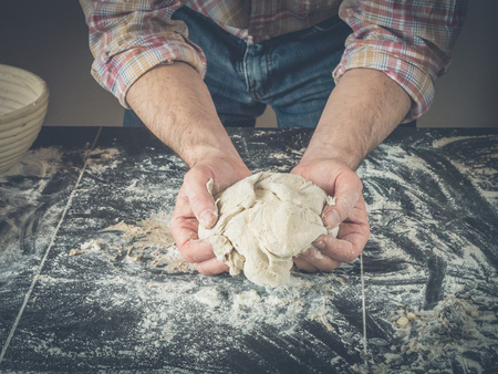 two hand holding fresh homemade dough for preparing bread or fresh pizza; a lot of flour at the background; situation is decorated with a wooden pulp bannetons