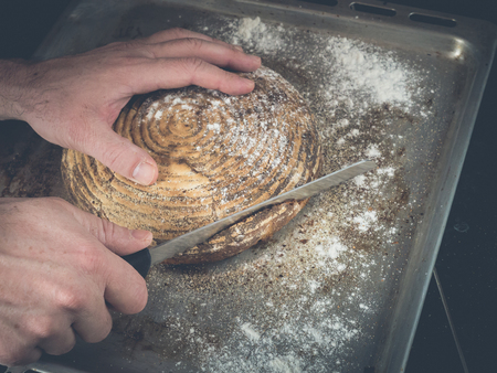 image shows a hand holding a homemade loaf of bread while cutting the bread into slices; situation is decorated with a lot of flour and crumps