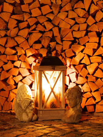 Lantern with burning candle in front of stack of logs