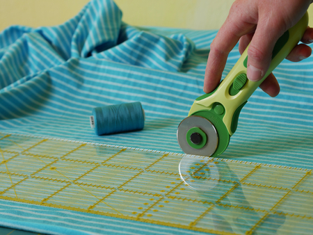 close up of cutting fabric with rotary cutter