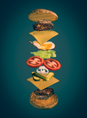 mage shows at the top of a burger decorated with toppings like fried egg, lettuce, cheese, patty, onions 스톡 콘텐츠