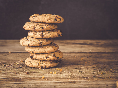 image shows a stack of best chocolate chip cookies decorated with orange zest on rustic wooden planks