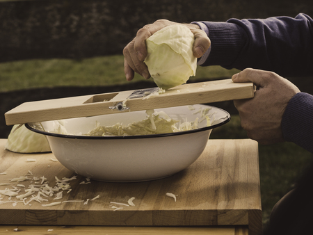 image shows how to make sauerkraut using a wooden cabbage shredder ; garden fence at the background Stock Photo
