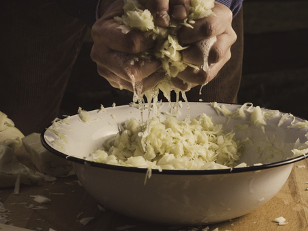 Hands squeezing a large handful of cabbage and brine is dripping down into a white bowl - preparation for sauerkraut
