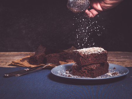 image shows fresh baked brownies on rustic wooden table; hand holding a dredger shaker; powdered sugar is flying over brownie cake