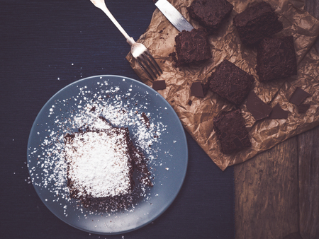 topview of homemade brownies on rustic wooden table decorated with baking paper and sterling silver fork and knife
