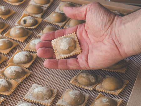 image shows hand with fresh homemade ravioli or pasta close to pasta squares,ravioli or tortellini during drying process
