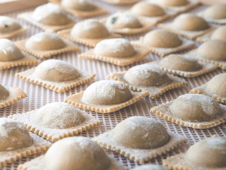 Image shows fresh made ravioli or pasta with nice sunshine from the window