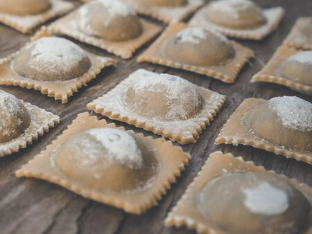 regional fresh handmade food and pasta like ravioli on wooden rustic background