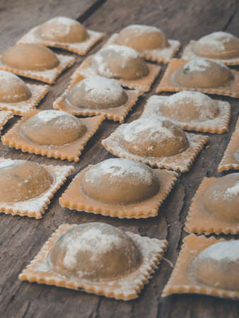 organic traditional pasta and ravioli handmade vegan filled with spinach and ricotta, on wooden background