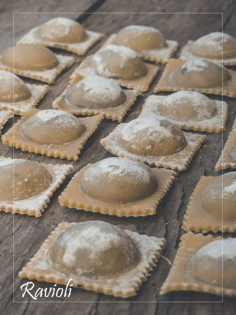 Organic traditional pasta and ravioli handmade vegan filled with spinach and ricotta on wooden Imagens