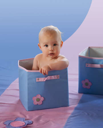 Adorable baby girl in blue box with flower