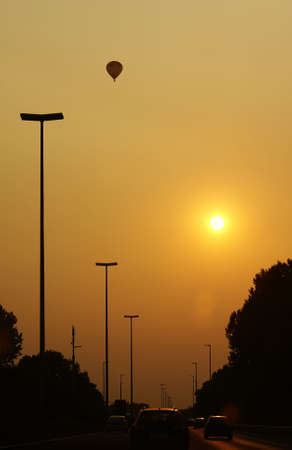 Silhouette of hot air balloon over highway while sun sets                 Stock Photo