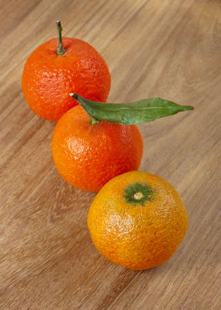 Three mandarins on wooden background close up, Clipping Path included