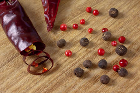 Allspice, Rose and Red hot pepper on wooden background close up