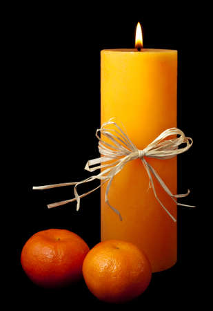 Lit candle with ribbon and two clementines isolated on black background