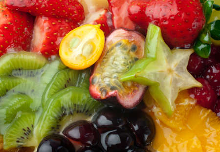 Macro of mixed fruits and berries in gel (raspberry, strawberry, red and white grapes, kiwi, clementines, pineapple, passionfruit, carambola) photo
