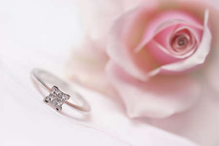 Diamond engagement ring with pink rose on background (shallow depth of field)