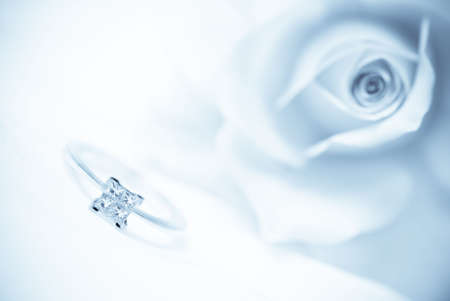 Diamond engagement ring with pink rose on background (shallow depth of field, blue toned image)