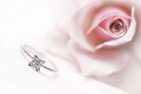 Close-up of diamond engagement ring with pink rose on background (shallow depth of field, bleached)