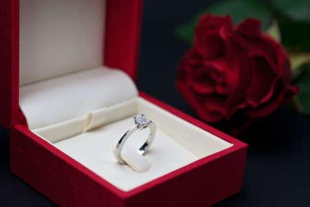 ring engagement: Anillo de compromiso de diamantes moderno en cuadro de joyer�a rojo sobre fondo negro (foco suave)