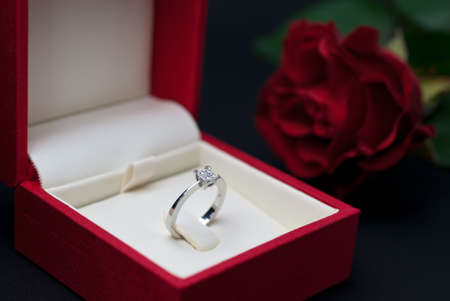 Modern diamond engagement ring in red jewellery box on black background (soft focus)