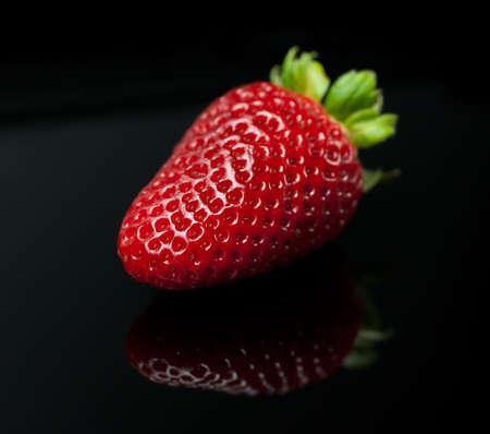 Fresh strawberry with leaf isolated on black background (macro)