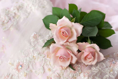 Three pink roses on wedding lace (shallow depth of field, copy space)