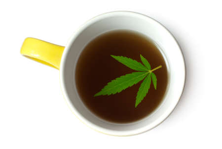 Green Cannabis (Marijuana) leaf in cup of tea isolated on white Stock Photo