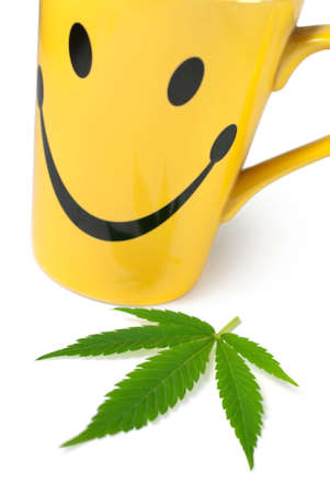 Green Cannabis (Marijuana) leaf next to yellow cup of tea on white background