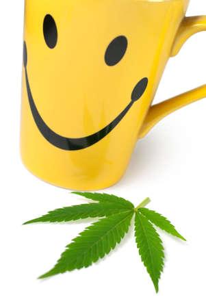 marijuana leaf: Green Cannabis (Marijuana) leaf next to yellow cup of tea on white background