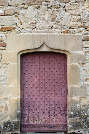 Old reddish door on a castle stone wall.