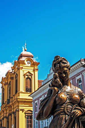 Old bronze statue on display at an exhibition of vintage in Unirii Square of Timisoara, Romania  In the background is German Dome