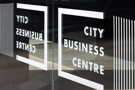 Glass door with inscriptions business from entering a building for business. Stock Photo
