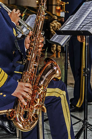 musical score: Officer military band playing the saxophone with musical score in front