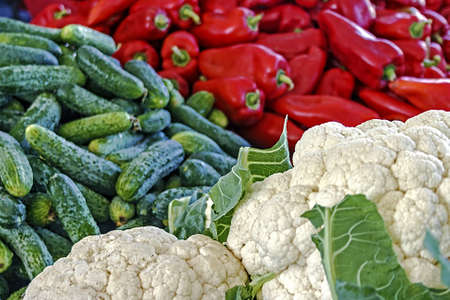 Cauliflower, cucumbers and red peppers exposed to sale in bulk in a market Stock Photo - 16252412