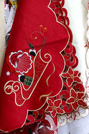 Centrepiece: Red and white tablecloths for Christmas dinner party, embroidered with various specific ornaments  Stock Photo