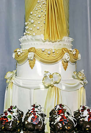 Wedding cake as columns, decorated with beads and roses  photo