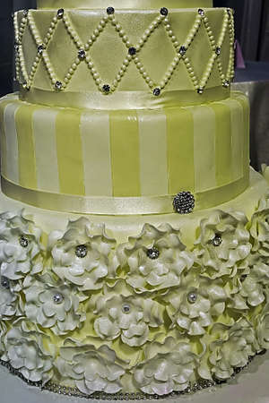 tiered: Wedding cake decorated with crystals, beads, decorative flowers and yellow ribbons