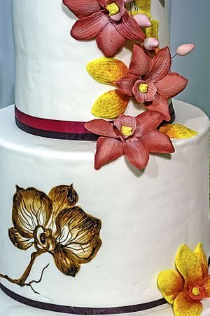 Wedding cake decorated with artificial flowers and painted  photo