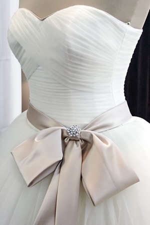 Detail of a wedding dress decorated with crystals, veils, ribbons and knot  photo