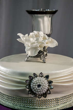 Wedding cake specially decorated with white beads, brooch flawer and candle